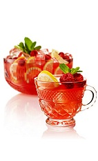 The Blushing Tease is a summer punch made from gin, lemon juice, simple syrup, lemon sherbet, green tea, raspberries, orange bitters and maraschino liqueur, and served from a small pitcher. Recipe serves 2.